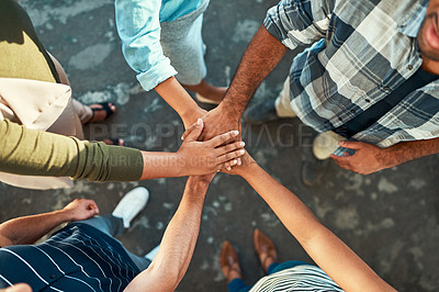 Buy stock photo High angle shot of an unrecognizable group of work colleagues forming a huddle with their hands while standing in the office at work