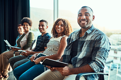 Buy stock photo Portrait of a group of young cheerful work colleagues seated on chairs next to each other in a row while making notes inside of the office during the day