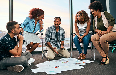 Buy stock photo Shot of a group of focussed young coworkers working together and brainstorming while being seated on the floor of the office at work during the day