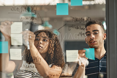 Buy stock photo Shot of two young designers brainstorming with notes on a glass wall in an office