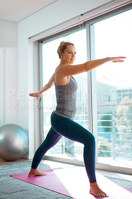 Buy stock photo High angle shot of an attractive mature woman stretching on a yoga mat at home