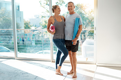 Buy stock photo Full length shot of an affectionate mature couple standing with their yoga mats at home