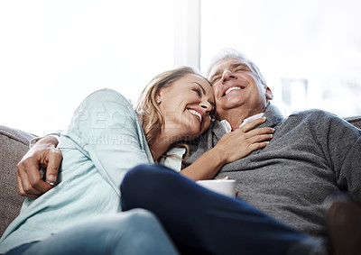 Buy stock photo Shot of a mature couple relaxing on the sofa together at home