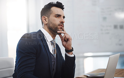 Buy stock photo Shot of a young businessman looking thoughtful in an office