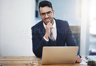 Buy stock photo Portrait of a young businessman working on a laptop in an office