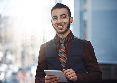 Buy stock photo Portrait of a young businessman working on a digital tablet in an office