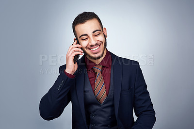 Buy stock photo Studio shot of a handsome young businessman on a call against a grey background