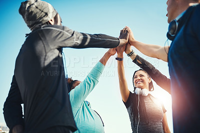 Buy stock photo Low angle shot of a group of sporty young people high fiving each other