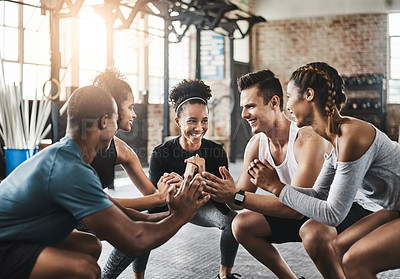 Buy stock photo Shot of a group of young people doing squats together during their workout in a gym