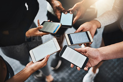 Buy stock photo Shot of a group of unrecognizable people using their mobile phones together in the gym