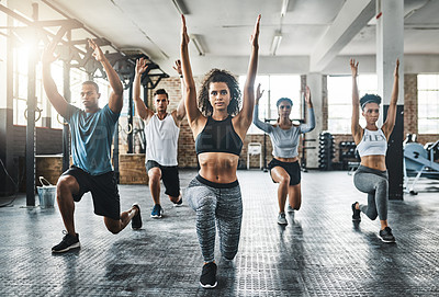 Buy stock photo Shot of a group of young people doing lunges together during their workout in a gym