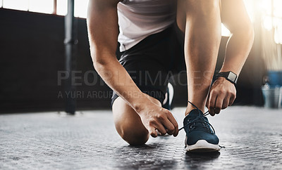 Buy stock photo Cropped shot of a man tying his shoelaces in a gym