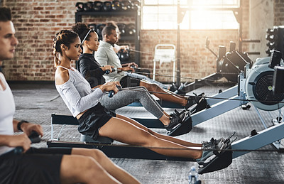 Buy stock photo Shot of a group of young people working out with rowing machines in the gym