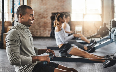 Buy stock photo Shot of a young man working out with a rowing machine in the gym