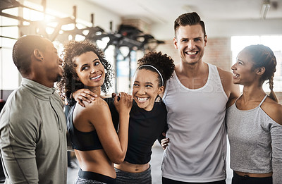 Buy stock photo Shot of a group of happy young people working out together in a gym