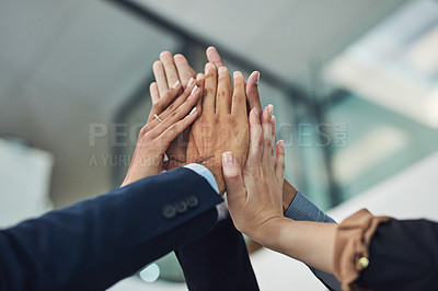 Buy stock photo Closeup of a group of unrecognizable businesspeople holding up their hands for a high five in the office during the day