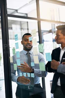Buy stock photo Cropped shot of two businessmen having a brainstorming session in a modern office