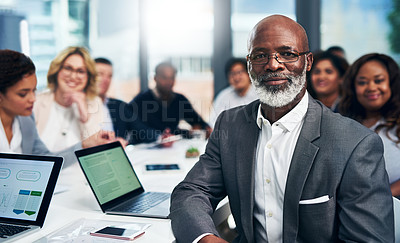 Buy stock photo Portrait of a mature businessman having a meeting with his colleagues in a modern office