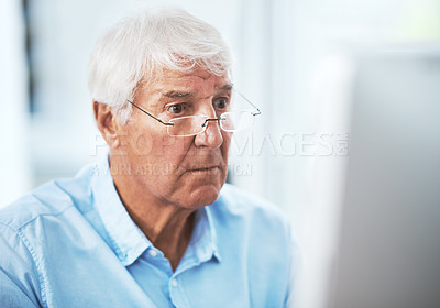 Buy stock photo Cropped shot of a handsome senior businessman working on his computer at home
