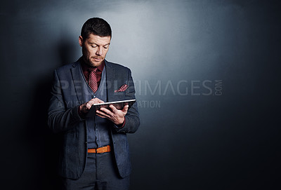 Buy stock photo Cropped shot of a handsome young businessman using his tablet while standing against a dark background