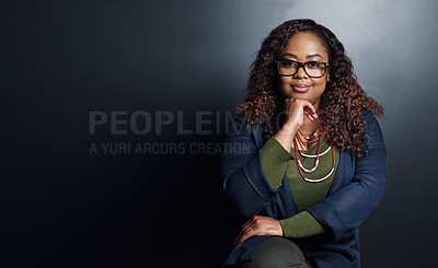 Buy stock photo Cropped portrait of an attractive young businesswoman sitting with her hand on her chin against a dark background