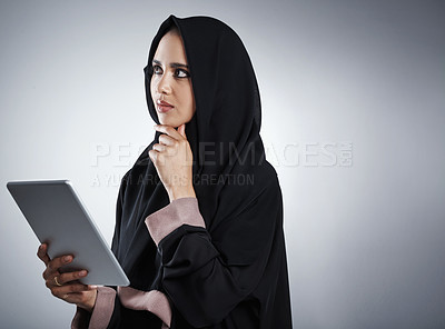 Buy stock photo Cropped shot of an attractive young businesswoman using her tablet while standing against a grey background