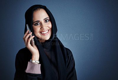 Buy stock photo Cropped portrait of an attractive young businesswoman making a call while standing against a dark background