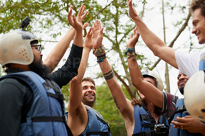 Buy stock photo Cropped shot of a group of young male friends giving each other a high five before they go white water rafting