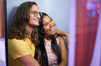 Buy stock photo Cropped shot of a beautiful young couple getting their photo taken in a photo booth while on a date