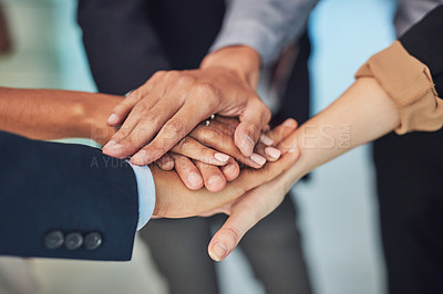 Buy stock photo Closeup of a group of unrecognizable businesspeople forming a huddle with their hands while standing in the office during the day