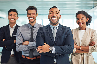 Buy stock photo Portrait of a group of cheerful young businesspeople standing with their arms folded in the office during the day