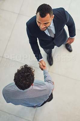 Buy stock photo High angle shot of two confident young businessmen shaking hands in agreement while standing in the office during the day