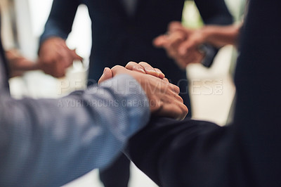 Buy stock photo Closeup of a group of unrecognizable businesspeople holding hands while standing in circle in the office during the day