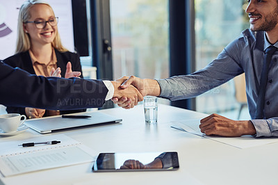Buy stock photo Cropped shot of a young businessman shaking hands with a colleague during a meeting in a modern office