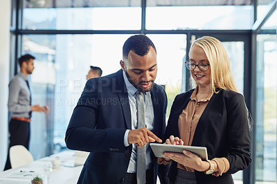 Buy stock photo Shot of a young businessman and businesswoman using a digital tablet together in the boardroom of a modern office