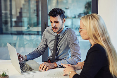 Buy stock photo Shot of a young businessman and businesswoman using a laptop together during a meeting in a modern office