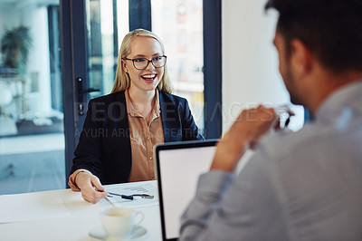 Buy stock photo Shot of a young businessman and businesswoman having a discussion in the boardroom of a modern office