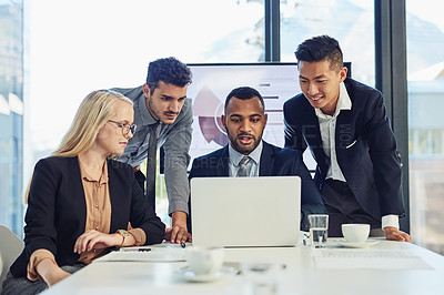 Buy stock photo Shot of a group of young businesspeople using a laptop during a meeting in the boardroom of a modern office