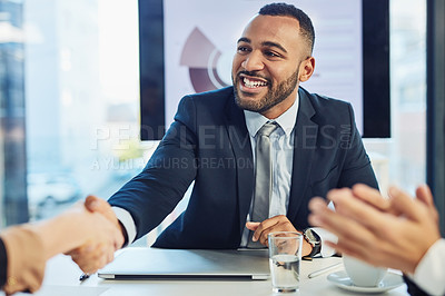 Buy stock photo Shot of a young businessman and businesswoman shaking hands during a meeting in a modern office