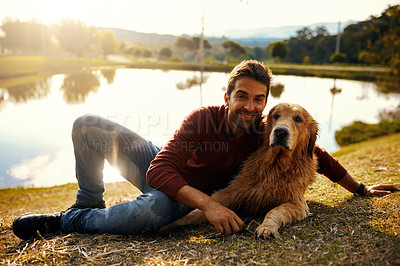 Buy stock photo Full length portrait of a handsome young man and his dog spending the day by a lake in the park
