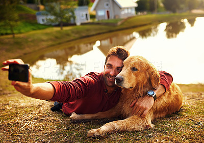 Buy stock photo Full length shot of a handsome young man and his dog taking selfies by a lake in the park
