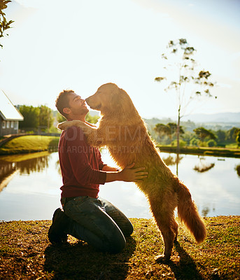 Buy stock photo Full length shot of a handsome young man and his dog spending the day by a lake in the park