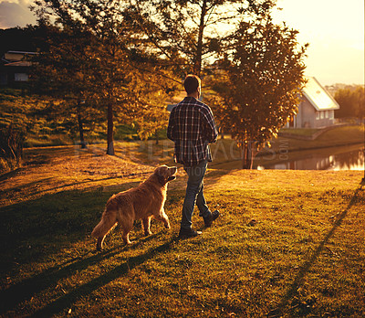 Buy stock photo Full length shot of a handsome young man walking with his dog around the park