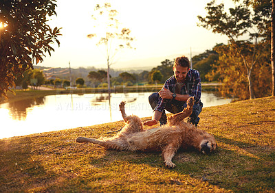 Buy stock photo Full length shot of a handsome young man playing with his dog by a lake in the park
