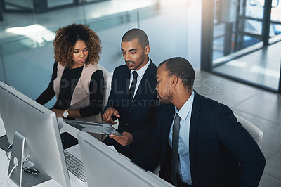 Buy stock photo High angle shot of three corporate businesspeople looking over some paperwork in their office