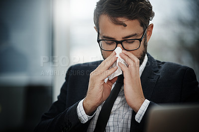 Buy stock photo Shot of a young businessman blowing his nose in an office