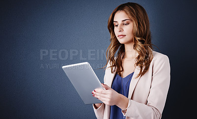 Buy stock photo Studio shot of an attractive young businesswoman using a digital tablet against a dark blue background