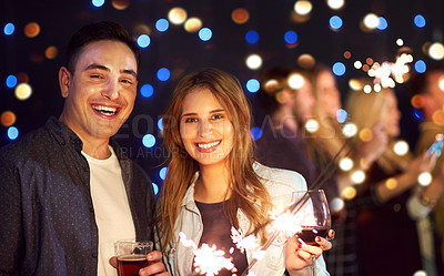 Buy stock photo Portrait of an attractive young couple having fun with sparklers at a nightclub