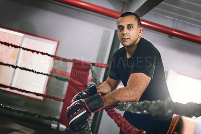 Buy stock photo Portrait of a confident young male boxer leaning against ropes inside of a boxing ring at a gym during the day