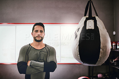 Buy stock photo Portrait of a confident young male boxer standing with his arms folded next to a punching bag inside of a gym during the day